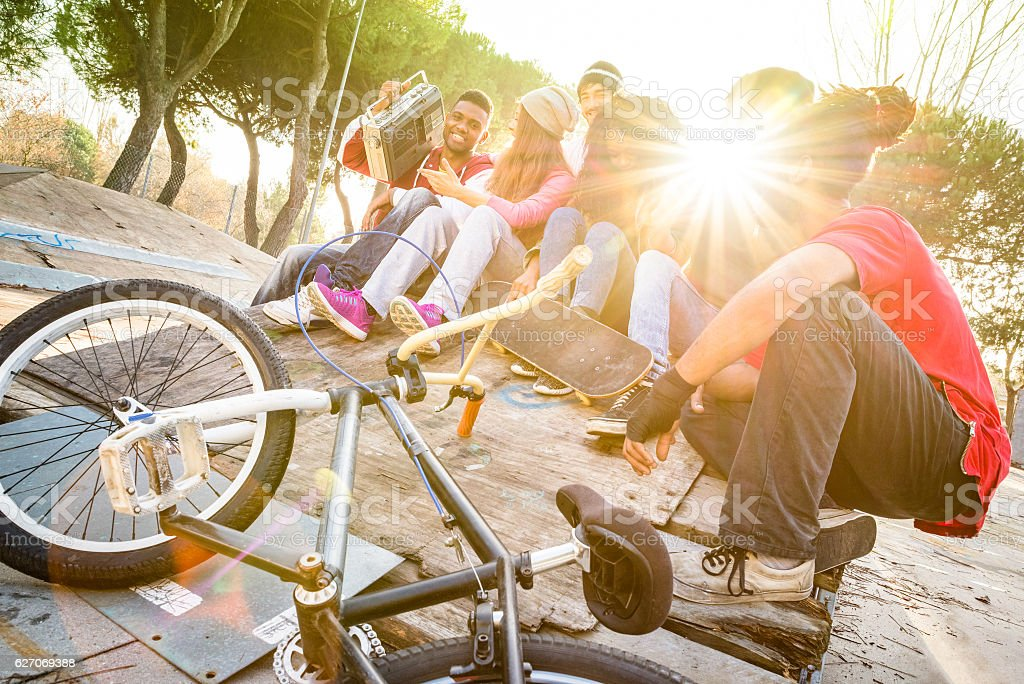 Group of trendy friends having fun at skate bmx park стоковое фото