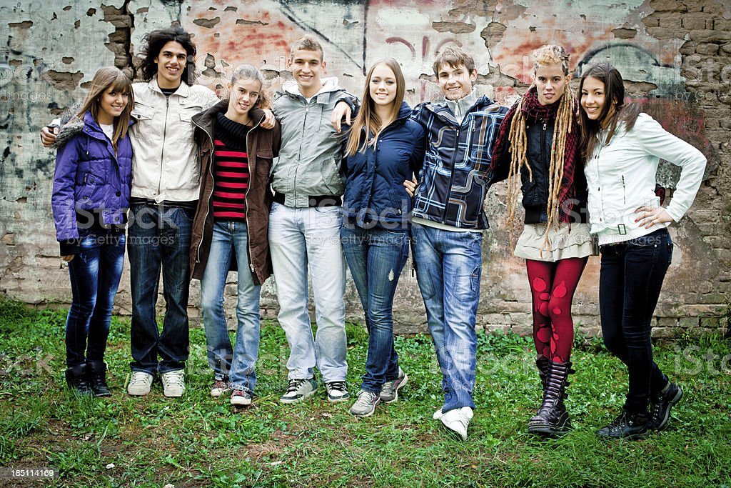 Group of trendy teenagers against grunge wall . royalty-free stock photo