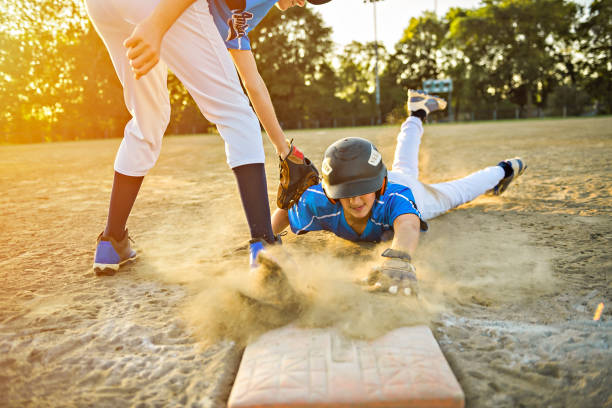 Group of two baseball players play together on the playground. On of them slide on the goal stock photo