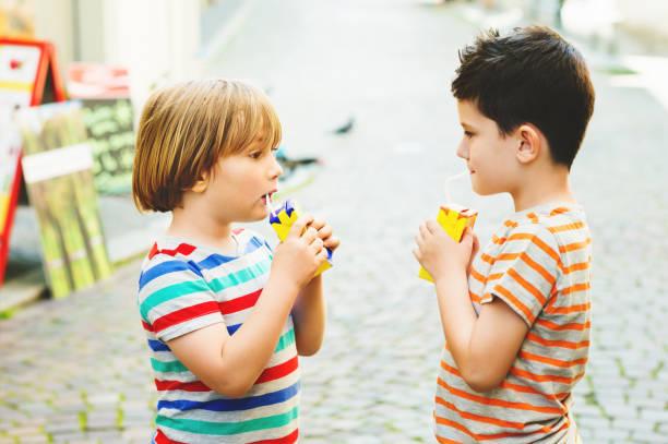 Groupe de deux petits garçons, boire du jus sur une chaude journée d'été - Photo