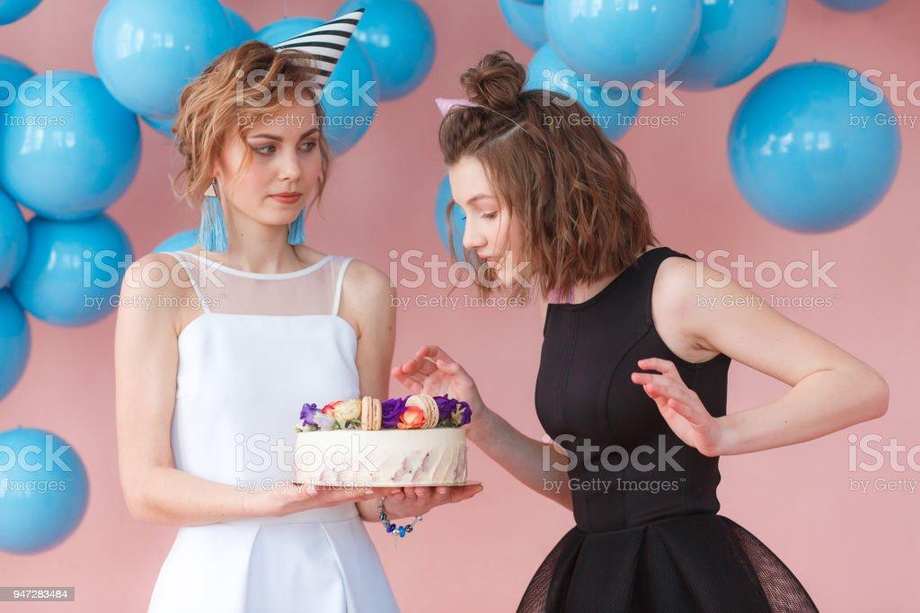 50e2177ae Grupo de dos chicas de moda lindo joven comer feliz cumpleaños cupcake rosa  decorado con flores