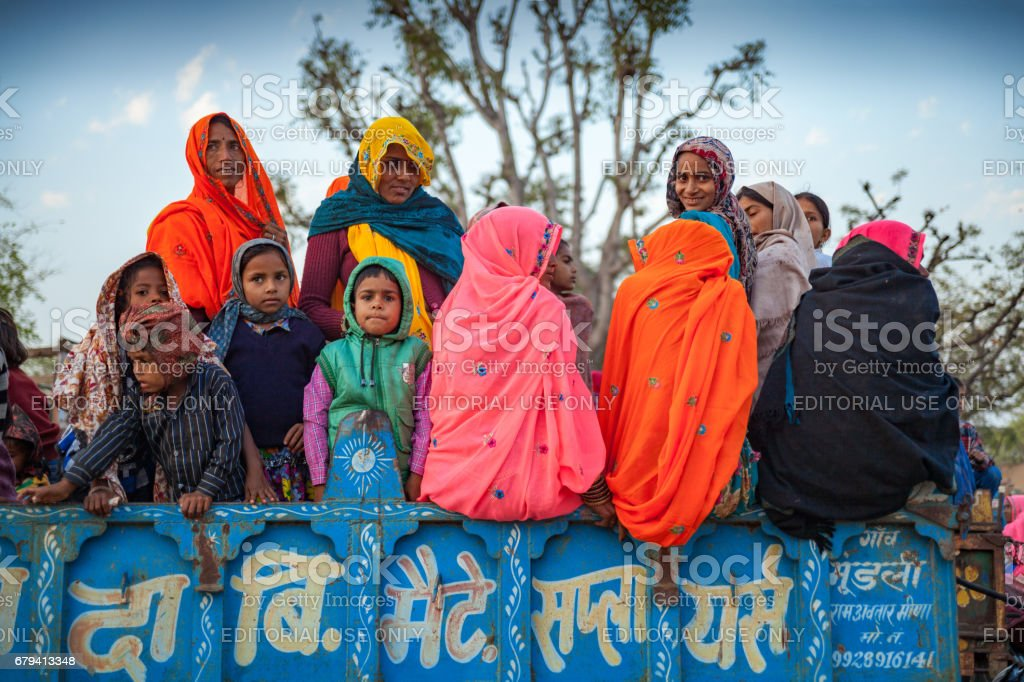 A group of unidentified Indian Rajasthani women and children have boarded a truck's while going to Chaksu fair in Jaipur royalty-free stock photo