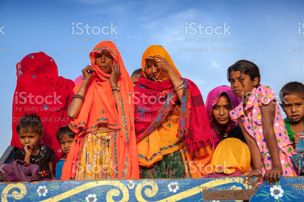 A group of unidentified Indian Rajasthani women and children have boarded on a tractor trolley and travelling to Chaksu Fair photo libre de droits
