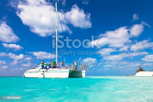 Group of unidentified tourists travel on a catamaran near the island of Kayo Largo.  White catamaran on a background of blue sky and azure water