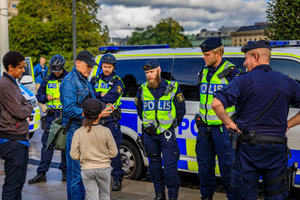 Group of uniformed Swedish male police officers talking to a little dark haired child in the center of Stockholm Sweden stock photo