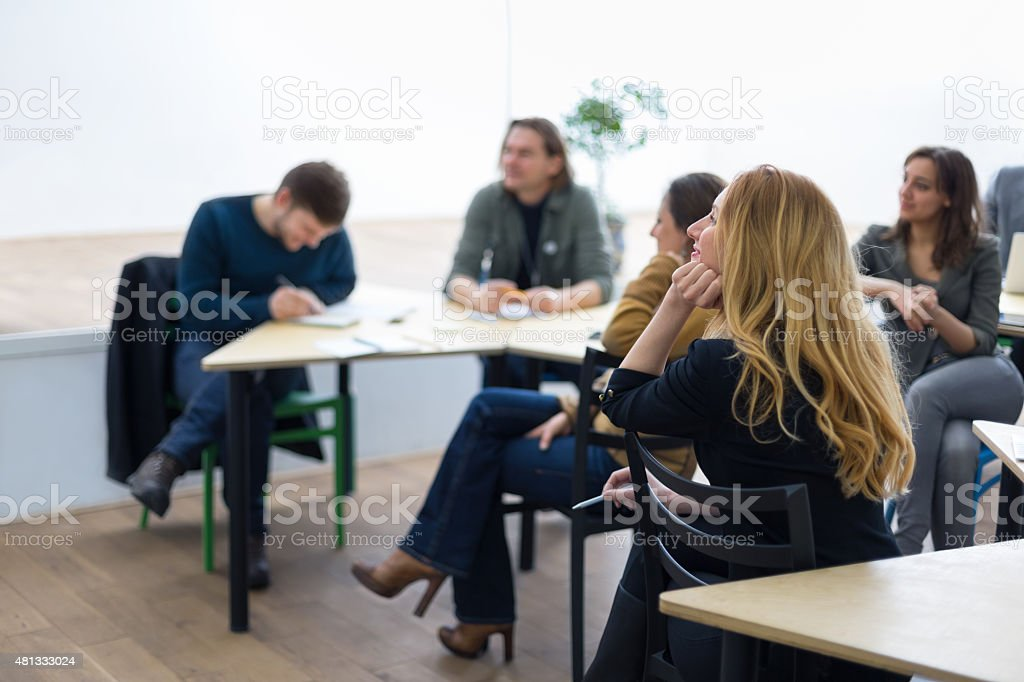 Group of university student sitting in classroom,  listening to stock photo