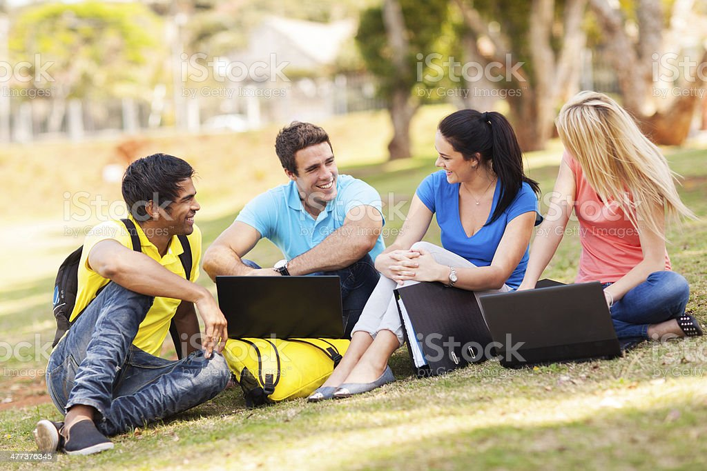 group of university students relaxing outdoors stock photo