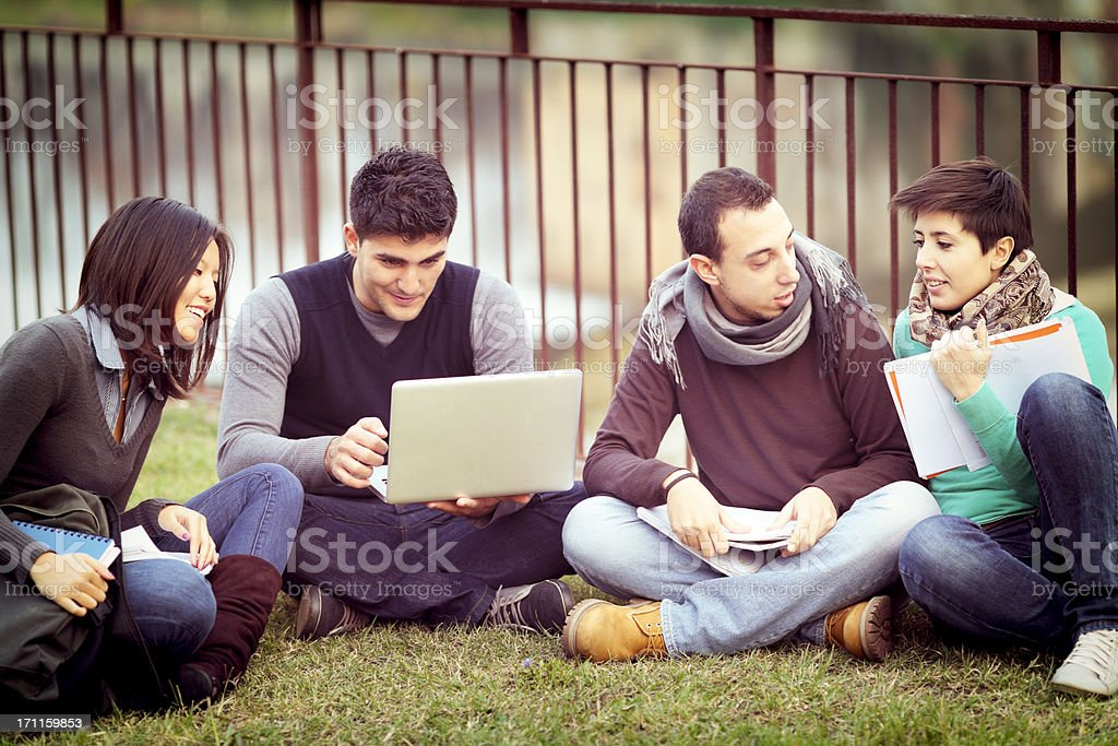 Group of university students using laptop outdoors royalty-free stock photo