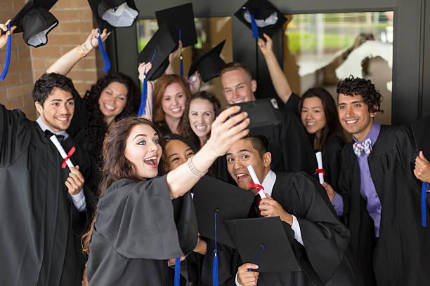 a group of university students wearing graduation gowns - high school bilder stock-fotos und bilder