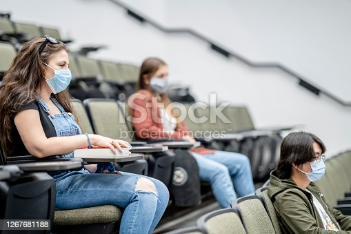 Multi-ethnic group of students wearing protective face masks while sitting in a lecture hall sitting 2 meters apart.