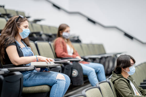 Group of university students wearing masks in class stock photo
