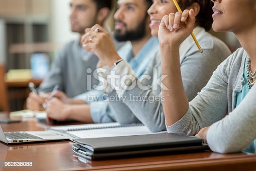 In this closeup, a group of unrecognizable university students sits at a table together in a lecture hall and look forward with interest as they listen to their professor give a lecture.