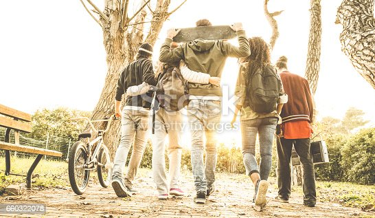 istock Group of urban friends walking in city skate park with backlighting at sunset - Youth and friendship concept with multiracial young people having fun together - Warm retro filter with soft focus 660322078