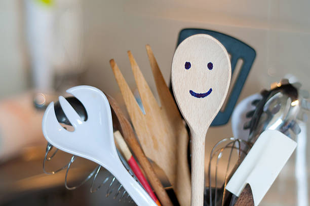 Group of utensils with smiling wooden spatula stock photo