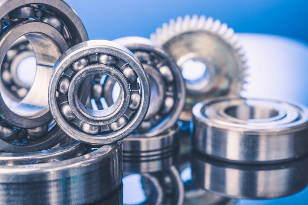 Group of various ball bearings and gears close up on nice blue background with reflections stock photo