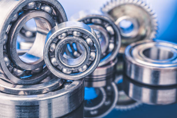 Group of various ball bearings close up on nice blue background with reflections stock photo