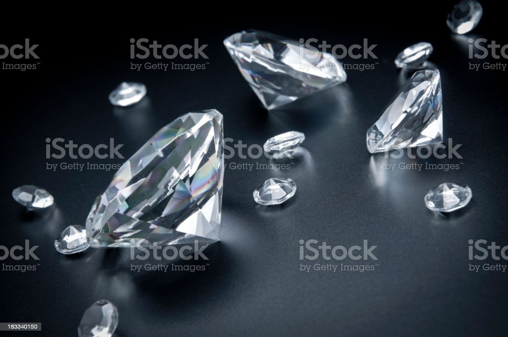 Group of various sized diamonds scattered on black background royalty-free stock photo