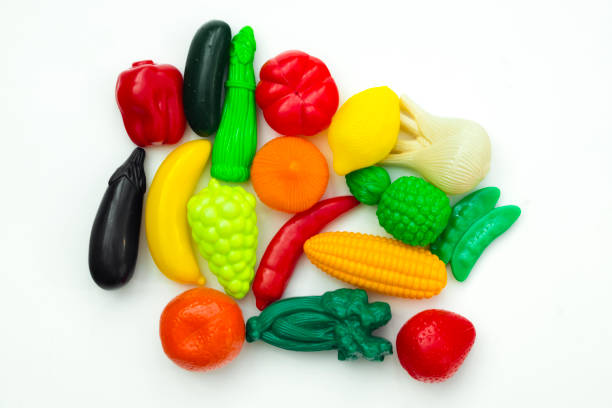 Group of vegetable and fruit plastic toys for children in isolated white background stock photo