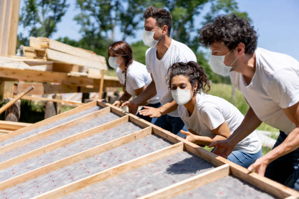 Group of volunteers building a house wearing a facemask during the COVID-19 pandemic stock photo