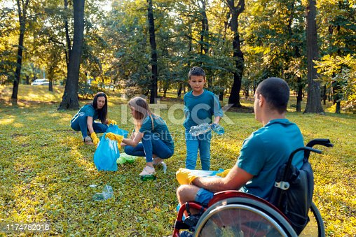 Team of volunteers cleaning wood from trash. Young Disabled Man on Wheelchair Cleaning, collects garbage with his friends during autumn day. Volunteer boy in yellow gloves collects garbage selective focus