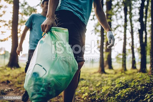 Group of  volunteers with garbage bags cleaning park area