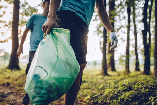 group of volunteers collecting garbage in park - sustainable living stock pictures, royalty-free photos & images