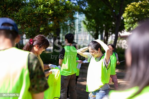 A group of volunteers are getting ready to clean a public park in Tokyo.