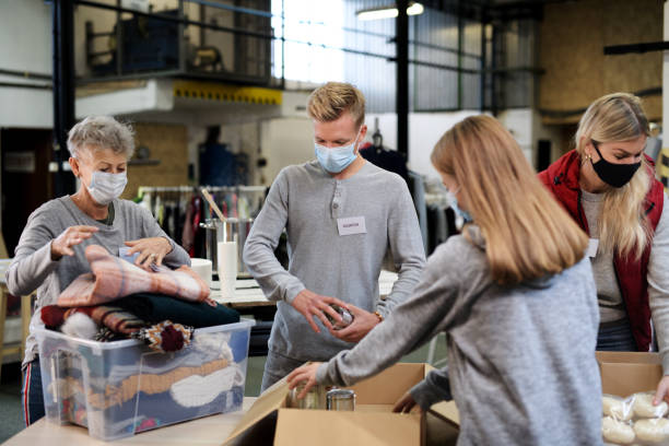 Group of volunteers in community charity donation center, food bank and coronavirus concept. stock photo