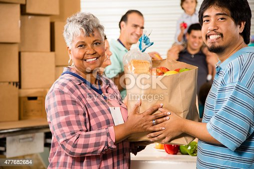 istock Group of volunteers provide groceries donations to needy families. Charity. 477682684
