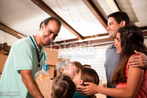 623523102 istock photo Group of volunteers provide groceries donations to needy families. Charity. 477705622