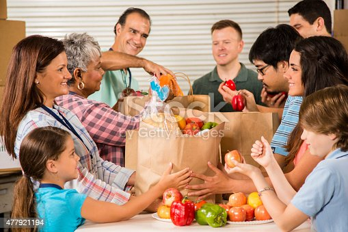 istock Group of volunteers provide groceries donations to needy families. Charity. 477921194