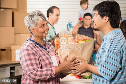 istock Group of volunteers provide groceries donations to needy families. Charity. 483824156