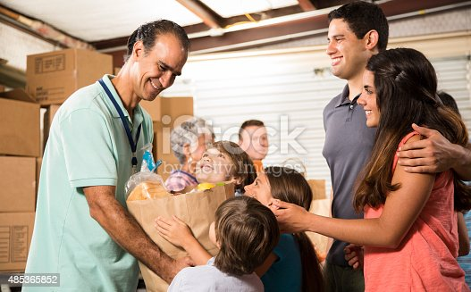 istock Group of volunteers provide groceries donations to needy families. Charity. 485365852