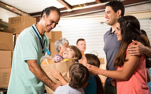 gruppe von freiwilligen mit lebensmittel spenden an bedürftigen familien. nächstenliebe. - bettler stock-fotos und bilder