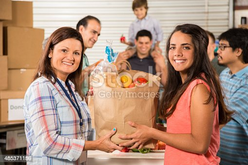 istock Group of volunteers provide groceries donations to needy families. Charity. 485371186