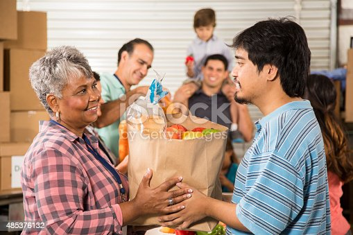 istock Group of volunteers provide groceries donations to needy families. Charity. 485376132