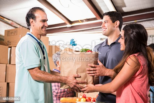 istock Group of volunteers provide groceries donations to needy families. Charity. 485405690