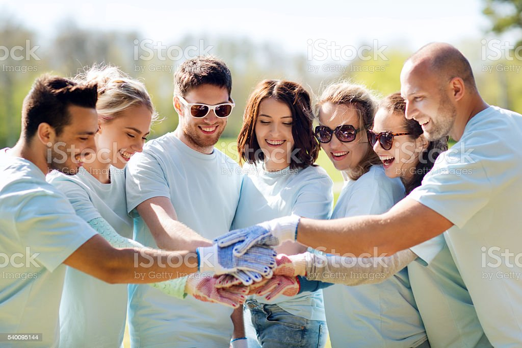 group of volunteers putting hands on top in park stock photo