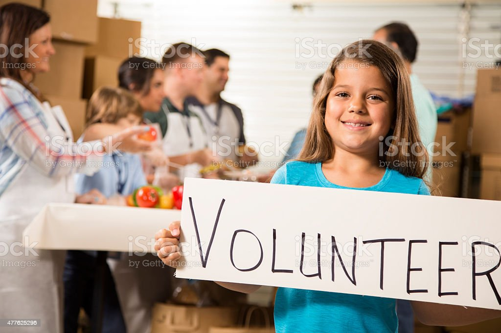 Multi-ethnic and mixed-age group of volunteers serve food to needy...