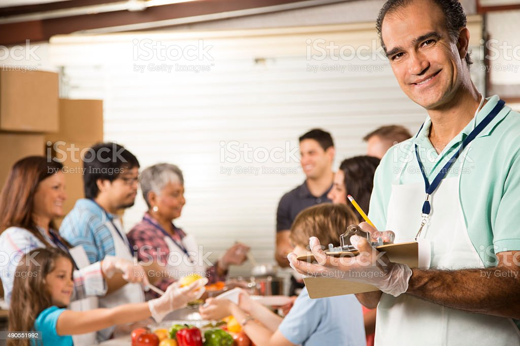 Group Of Volunteers Serve Food At Community Soup Kitchen. Charity.  Royalty Free Stock