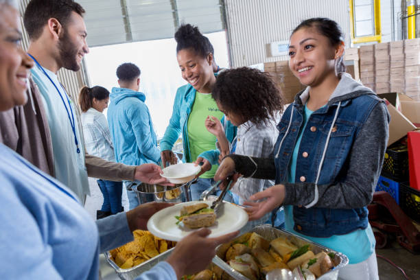 Group of volunteers serve meal at soup kitchen stock photo