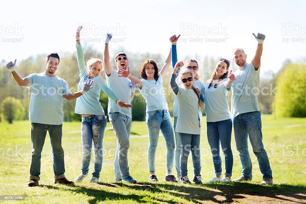 group of volunteers showing thumbs up in park stock photo