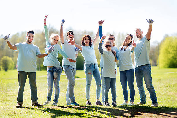 group of volunteers showing thumbs up in park - volunteer stock photos and pictures