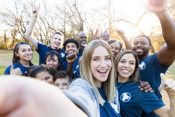 group of volunteers take selfie during cleanup event - charity and relief work stock pictures, royalty-free photos & images