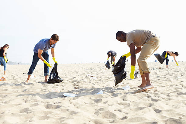 Group Of Volunteers Tidying Up Rubbish On Beach Group Of Volunteers Tidying Up Rubbish On Beach Picking Up Litter. environmental cleanup stock pictures, royalty-free photos & images