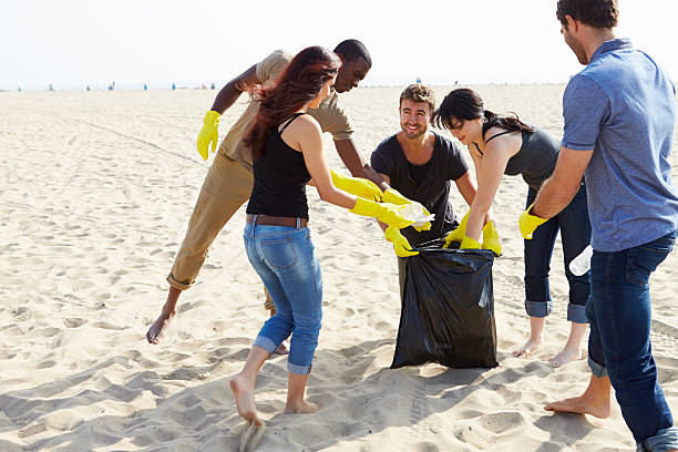 Group Of Volunteers Tidying Up Rubbish On Beach Group Of Volunteers Tidying Up Rubbish On Beach Wearing Rubber Gloves. environmental cleanup stock pictures, royalty-free photos & images
