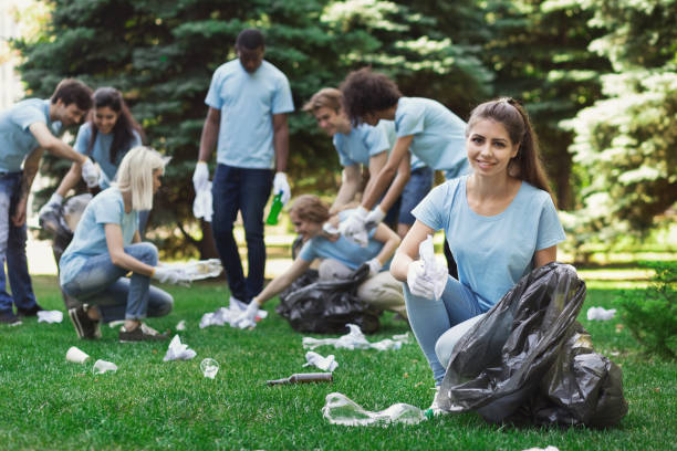 group of volunteers with garbage bags cleaning park - ambientalista foto e immagini stock