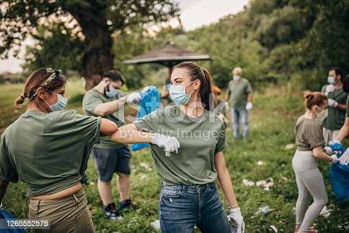 istock Group of volunteers with surgical masks cleaning nature together 1265552575
