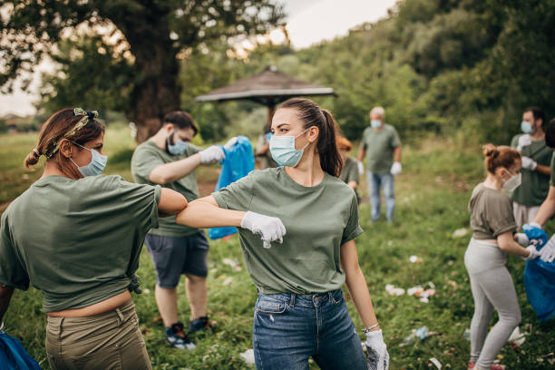 group of volunteers with surgical masks cleaning nature together - charity and relief work stock pictures, royalty-free photos & images