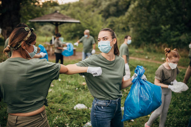 Group of volunteers with surgical masks cleaning nature together stock photo
